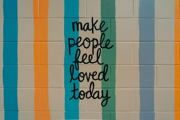 brightly colored wall with quote Make People Feel Loved Today